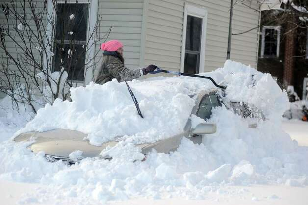 Abbie J. Haie digs out her grandmother's car at their home on Tuesday, Nov. 18, 2014 in  Edwards, N.Y.  A new blast of lake-effect snow pounded Buffalo for a third day piling more misery on a city already buried by an epic, deadly snowfall that could leave some areas with nearly 8 feet of snow on the ground when it's all done. (AP Photo/The Watertown Daily Times, Melanie Kimbler Lago)   ORG XMIT: NYWAT204 Photo: Melanie Kimbler Lago / The Watertown Daily Times