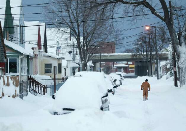 A man walks along a snow-covered street on Thursday, Nov. 20, 2014, in Buffalo, N.Y. A new blast of lake-effect snow pounded Buffalo for a third day piling more misery on a city already buried by an epic, deadly snowfall that could leave some areas with nearly 8 feet of snow on the ground when it's all done. (AP Photo/Mike Groll) ORG XMIT: NYMG102 Photo: Mike Groll / AP