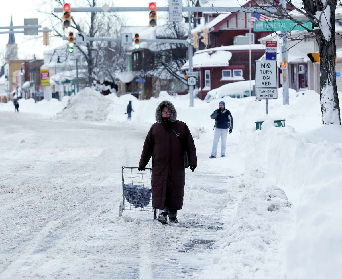 A woman walks along a snow-covered street in the south Buffalo area on Thursday, Nov. 20, 2014, in Buffalo, N.Y. A new blast of lake-effect snow pounded Buffalo for a third day piling more misery on a city already buried by an epic, deadly snowfall that could leave some areas with nearly 8 feet of snow on the ground when it's all done. (AP Photo/Mike Groll) ORG XMIT: NYMG112