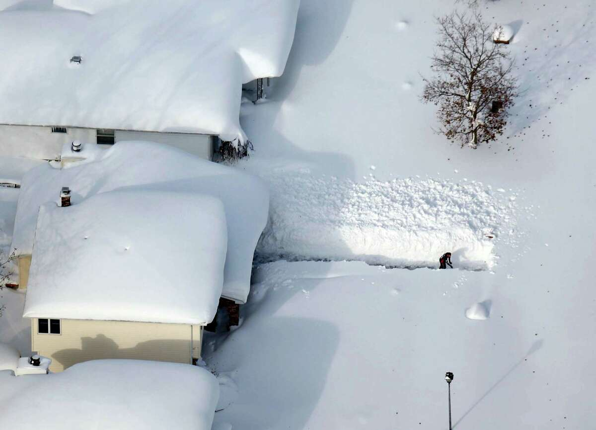 A man digs out his driveway in Depew, N.Y.,Wednesday, Nov. 19, 2014. The Buffalo area found itself buried under as much as 5½ feet of snow Wednesday, with another lake-effect storm expected to bring 2 to 3 more feet by late Thursday. (AP Photo/The Buffalo News, Derek Gee) MANDATORY CREDIT; TV OUT; MAGS OUT; MANDATORY CREDIT; BATAVIA DAILY NEWS OUT; DUNKIRK OBSERVER OUT; JAMESTOWN POST-JOURNAL OUT; LOCKPORT UNION-SUN JOURNAL OUT; NIAGARA GAZETTE OUT; OLEAN TIMES-HERALD OUT; SALAMANCA PRESS OUT; TONAWANDA NEWS OUT ORG XMIT: NYBUE304