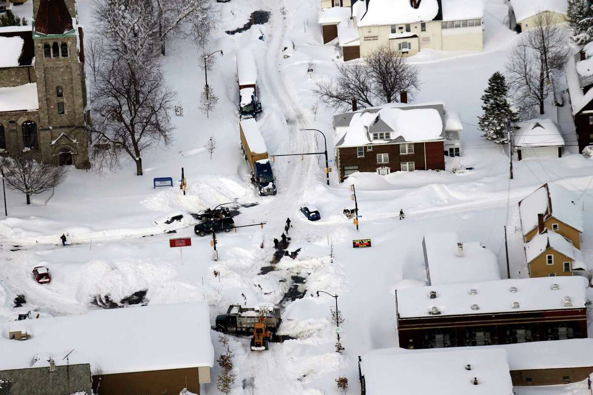 Cars make their way through South Buffalo, N.Y.,Wednesday, Nov. 19, 2014. The Buffalo area found itself buried under as much as 5½ feet of snow Wednesday, with another lake-effect storm expected to bring 2 to 3 more feet by late Thursday. (AP Photo/The Buffalo News, Derek Gee) TV OUT; MAGS OUT; MANDATORY CREDIT; BATAVIA DAILY NEWS OUT; DUNKIRK OBSERVER OUT; JAMESTOWN POST-JOURNAL OUT; LOCKPORT UNION-SUN JOURNAL OUT; NIAGARA GAZETTE OUT; OLEAN TIMES-HERALD OUT; SALAMANCA PRESS OUT; TONAWANDA NEWS OUT ORG XMIT: NYBUE307
