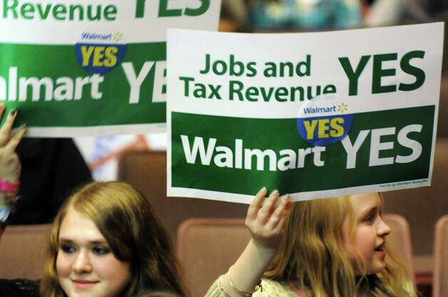 Residents Amanda Cox, 16, left, and her sister Mallory Cox, 12, show their support during a public hearing on a proposed 137,000 square-foot Walmart on Thursday, Nov. 20, 2014, at Ballston Spa High in Ballston Spa, N.Y. (Cindy Schultz / Times Union) Photo: Cindy Schultz / 00029572A