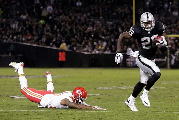 Oakland Raiders running back Latavius Murray (28) runs past Kansas City Chiefs cornerback Sean Smith on an 11-yard touchdown run during the first quarter of an NFL football game in Oakland, Calif., Thursday, Nov. 20, 2014. (AP Photo/Marcio Jose Sanchez) ORG XMIT: OAS103 Photo: Marcio Jose Sanchez / AP