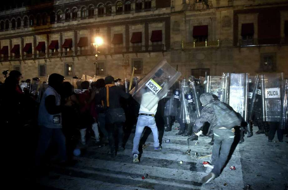 Students face riot police outside the National Palace in Mexico City during a protest over the 43 missing students. Photo: YURI CORTEZ / Yuri Cortez / Getty Images / YURI CORTEZ