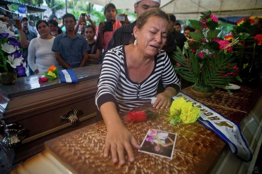 Teresa de Jesus Munoz, mother of Maria Jose Alvarado, 19, grieves over the beauty queen's casket during a wake for Maria and her sister Sofia outside the family's home in Santa Barbara, Honduras. Photo: Esteban Felix, STF / Associated Press / AP