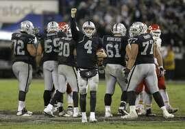 Oakland Raiders quarterback Derek Carr (4) celebrates after the Raiders beat the Kansas City Chiefs in an NFL football game in Oakland, Calif., Thursday, Nov. 20, 2014. The Raiders won 24-20. (AP Photo/Ben Margot)