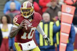 Washington Redskins quarterback Robert Griffin III (10) scrambles with the ball during the first half of an NFL football game against the Tampa Bay Buccaneers in Landover, Md., Sunday, Nov. 16, 2014. (AP Photo/Mark Tenally)
