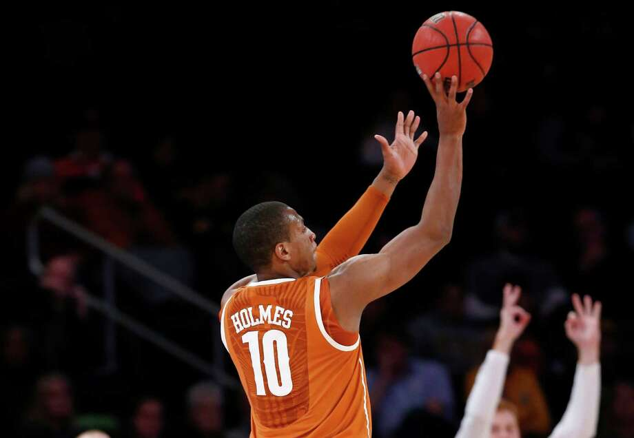 Texas forward Jonathan Holmes, an Antonian High product, shoots a 3-pointer against Iowa in New York. Holmes scored 17 of his 19 points in the second half. Photo: Kathy Willens, STF / Associated Press / AP