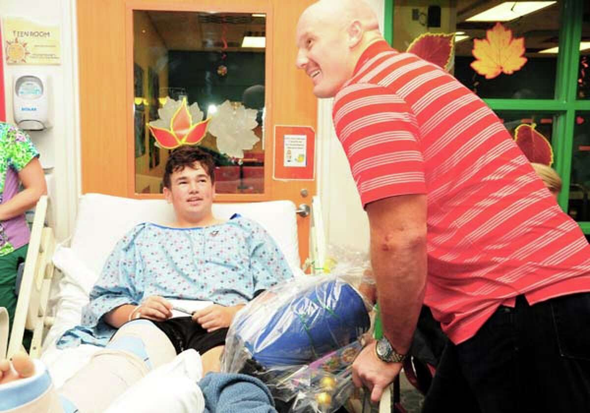 Houston Texans center Chris Myers chats with Children's Memorial Hermann Hospital pediatric patient 13-year-old Harrison Fason before giving him a
