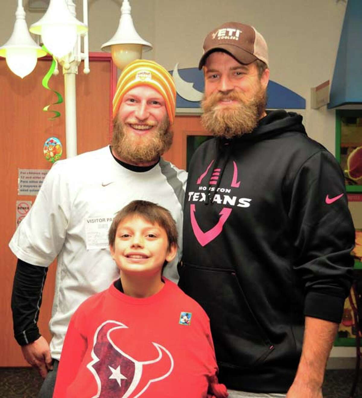 Anthony Eisfelt (left), father of Children's Memorial Hermann Hospital pediatric patient nine-year-old Cameron (front), was temporarily mistaken by some event attendees for Houston Texans quarterback Ryan Fitzpatrick (right).