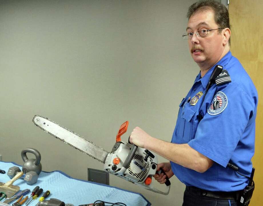 Ron Babbitt of the TSA holds a chainsaw surrendered from a passenger's carry-on recently at Albany International Airport Friday Nov. 21, 2014, in Colonie, NY.  (John Carl D'Annibale / Times Union) Photo: John Carl D'Annibale / 00029562A