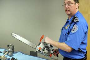 Ron Babbitt of the TSA holds a chainsaw surrendered from a passenger's carry-on recently at Albany International Airport Friday Nov. 21, 2014, in Colonie, NY.  (John Carl D'Annibale / Times Union)