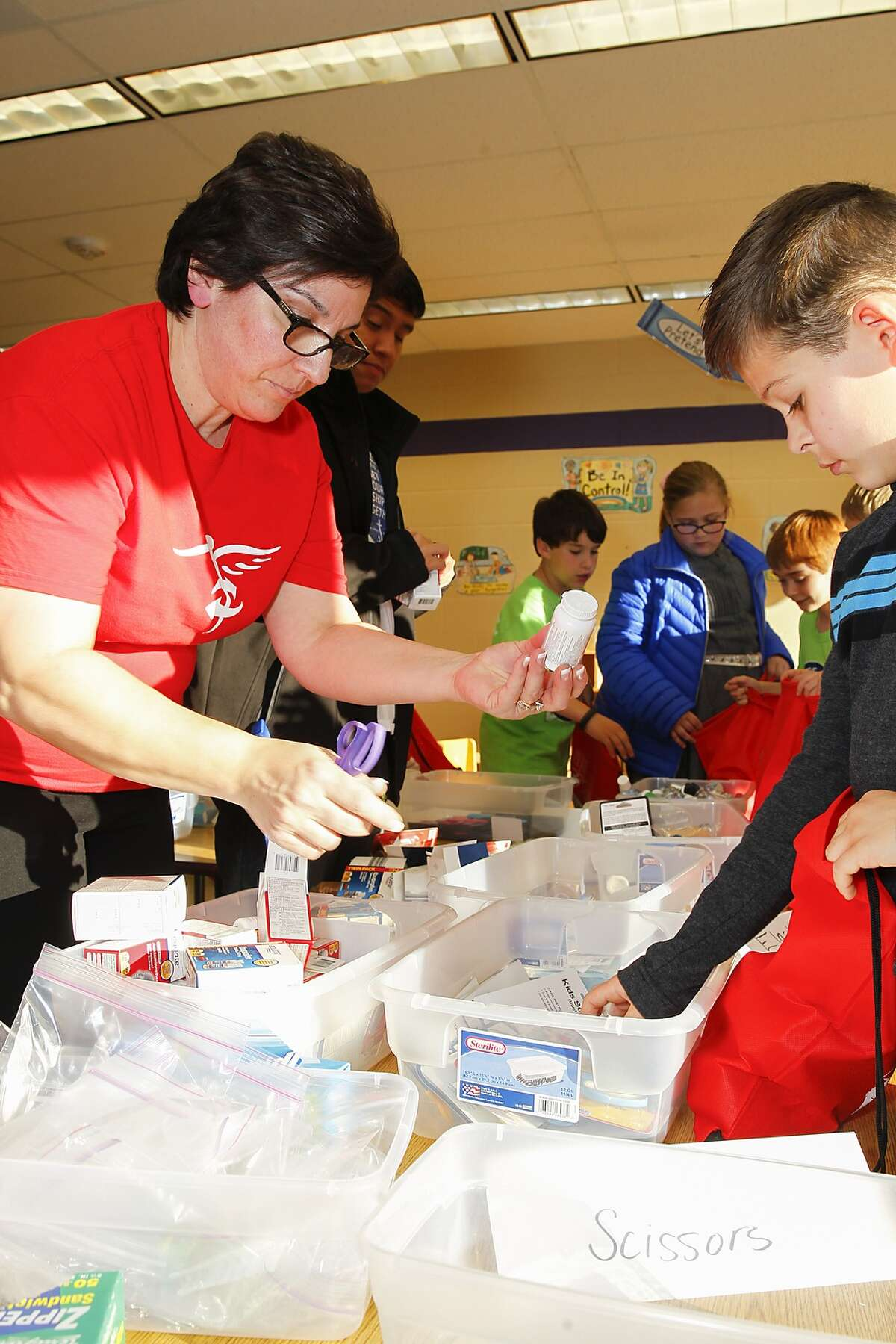Janet Thomason, a parent volunteer, assists Michael Bone, a fifth-grader at Pattison Elementary School in Katy, in packing medical kits on Nov. 17 for the Katy for Kids project. The project will send kits all over the world and is sponsored by the James E. Taylor High School National Honor Society.Janet Thomason, a parent volunteer, assists Michael Bone, a fifth-grader at Pattison Elementary School in Katy, in packing medical kits on Nov. 17 for the Katy for Kids project. The project will send kits all over the world and is sponsored by the James E. Taylor High School National Honor Society.