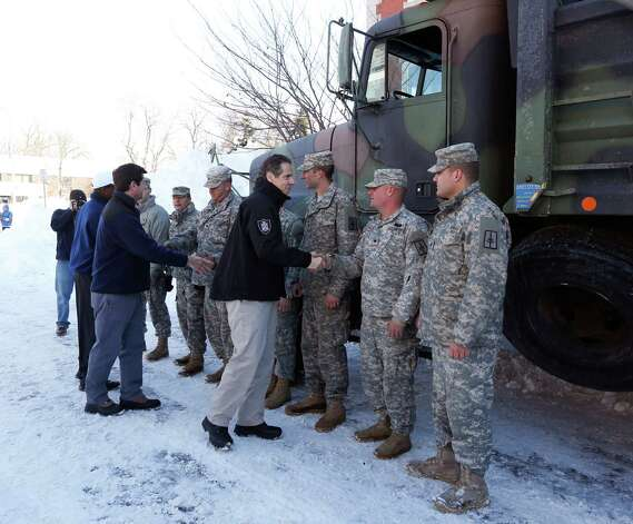 New York Gov. Andrew Cuomo thanks National Guard members in south Buffalo for their help clearing streets after heavy lake-effect snowstorms in western New York on Friday, Nov. 21, 2014, in Buffalo, N.Y. A snowfall that brought huge drifts and closed roads in the Buffalo area finally ended Friday, yet residents still couldn't breathe easy, as the looming threat of rain and higher temperatures through the weekend and beyond raised the possibility of floods and more roofs collapsing under the heavy loads. (AP Photo/Mike Groll) ORG XMIT: NYMG117 Photo: Mike Groll, AP / AP