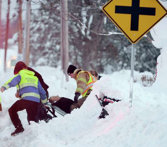 Emergency crews in Elma respond to a first aid call as they navigate their way through the snow on Bowen Rd. in Elma, N.Y. Friday, Nov. 21, 2014. Rescue efforts have been hampered as a result of the epic snowfall. (AP Photo/Gary Wiepert) ORG XMIT: NYGW101 Photo: Gary Wiepert, AP / FR170498 AP