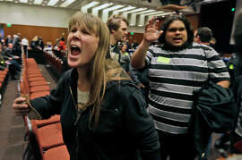 Amelia Itnyre, 23, and Sebastian Cano, 21, students at University of California Davis, react after the vote to raise tuition fees was announced during the UC Regents meeting in San Francisco, Thursday, Nov. 20, 2014. The Regents approved raising tuition by as much as 5 percent in each of the next five years unless the state devotes more money to the 10-campus system. (AP Photo/Eric Risberg)