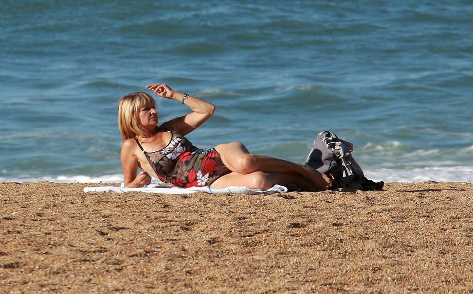 WORKING ON HER PRE-CHRISTMAS TAN:November is not normally a sunbathing month in France, but when the temperature climbs over the 22 degrees Celsius (70 F) in Anglet, sweaters are shed in favor of swimsuits. Photo: Bob Edme, Associated Press