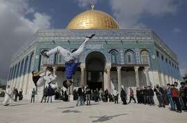 TOPSHOTS Palestinian youths pratice parkour outside the Dome of the Rock mosque at the Al-Aqsa mosque compound following Friday prayers in the Old City of Jerusalem on November 21, 2014. Tens of thousands of Muslims prayed at Jerusalem's flashpoint Al-Aqsa mosque Friday, after Israeli eased age restrictions on entry for a second straight week despite high tension after a wave of violence. AFP PHOTO/AHMAD GHARABLIAHMAD GHARABLI/AFP/Getty Images