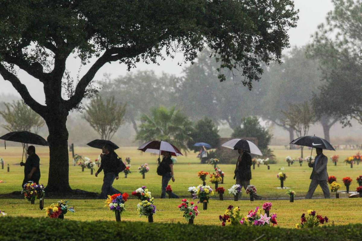Mourners cross the Grand View Memorial Park on their way to the funeral home due to a full parking lot for the funeral's of brothers, Robert Tisnado, 39, and Gilbert
