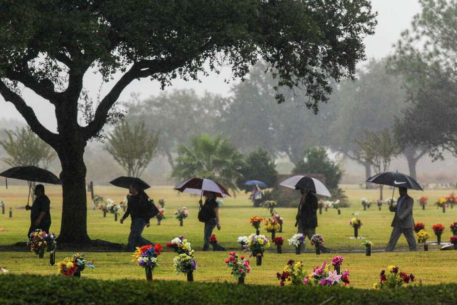 """Mourners cross the Grand View Memorial Park on their way to the funeral home due to a full parking lot for the funeral's of brothers, Robert Tisnado, 39, and Gilbert """"Gibby"""" Tisnado, 48 who died in a hazardous chemical leak at a DuPont plant in La Porte last weekend. / Photo: Johnny Hanson 