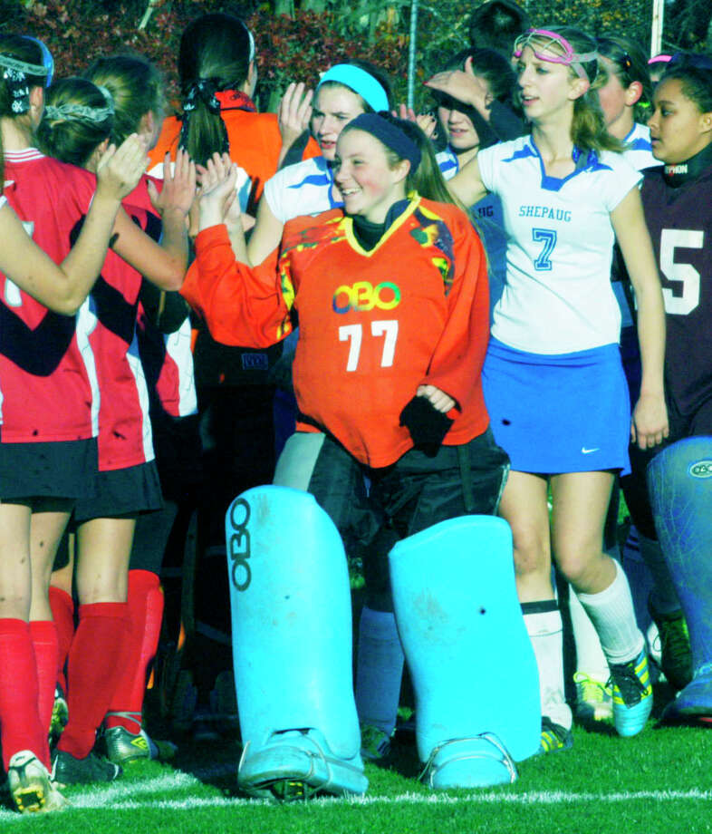 Spartan goaltender Rachel Genua, Kelsey Johnson and Kaitlyn Smith (7) lead their teammates exchanging respects with the Highlanders following Shepaug Valley School field hockey's state class 'S' tournament 3-1 victory over Northwestern in Washington, Nov. 3, 2014 Photo: Norm Cummings / The News-Times