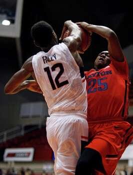 UConn forward Kentan Facey, left, blocks a shot from Dayton forward Kendall Pollard during a NCAA college basketball game in San Juan, Puerto Rico, Friday, Nov. 21, 2014. Photo: Ricardo Arduengo, AP / Associated Press