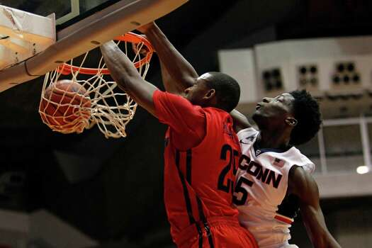 Dayton forward Kendall Pollard, left, slam dunks the ball past UConn guard Daniel Hamilton during a NCAA college basketball game in San Juan, Puerto Rico, Thursday, Nov. 20, 2014. Photo: Ricardo Arduengo, AP / Associated Press