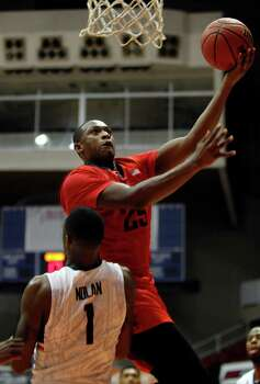 Dayton forward Kendall Pollard, top, goes to the basket against UConn forward Phillip Nolan during a NCAA college basketball game in San Juan, Puerto Rico, Friday, Nov. 21, 2014. Photo: Ricardo Arduengo, AP / Associated Press