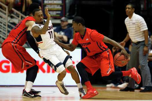 Dayton guard Scoochie Smith, right, dribbles past UConn guard Ryan Boatright during a NCAA college basketball game in San Juan, Puerto Rico, Friday, Nov. 21, 2014. Photo: Ricardo Arduengo, AP / Associated Press