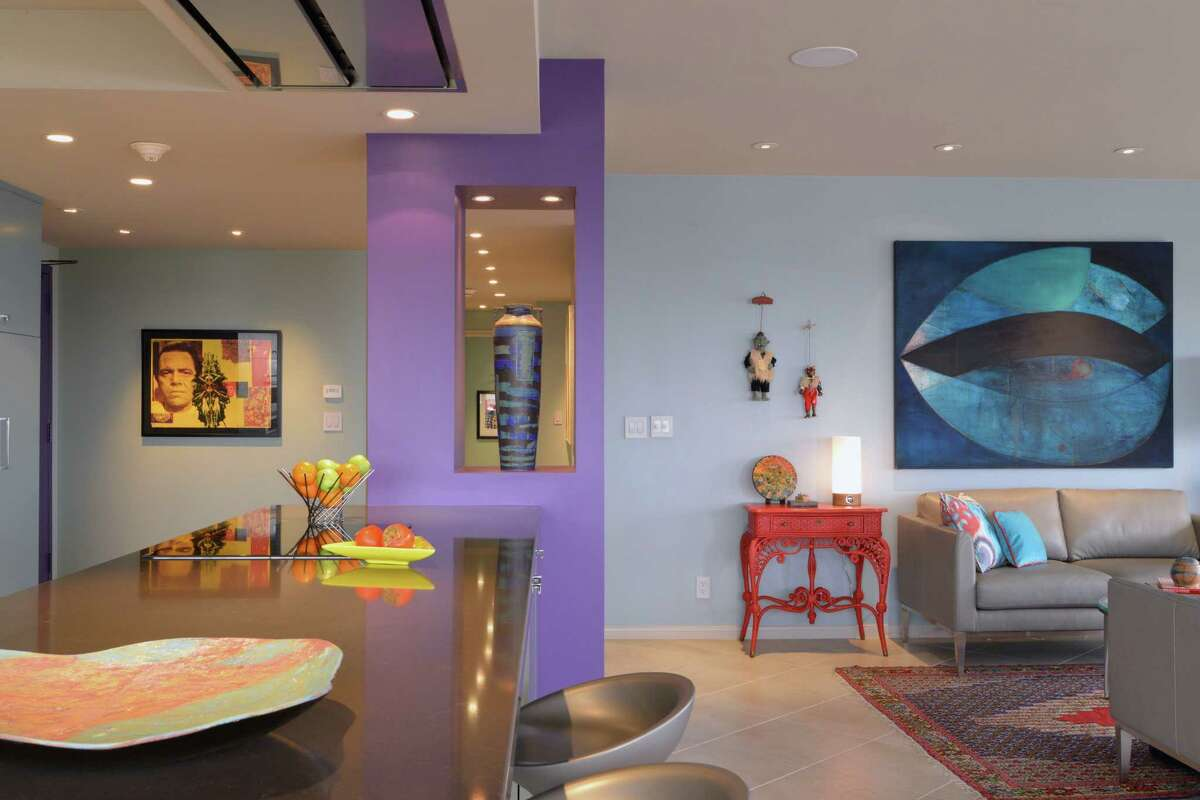 Sydney Greenblatt and Ward White's Houston high-rise condo is filled with pops of purple and cool blue hues. Much of the art around the home is the work of Greenblatt's daughter, and her daughter's artist friends.