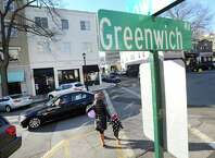 A woman and child hold hands as they cross Greenwich Avenue in the business district of Greenwich, Conn., Friday afternoon, Nov. 21, 2014. Greenwich was named the safest big city in the state of Connecticut by researchers at ValuePenguin, coming in with the lowest crime rate for cities with a population of more than 45,000 people.