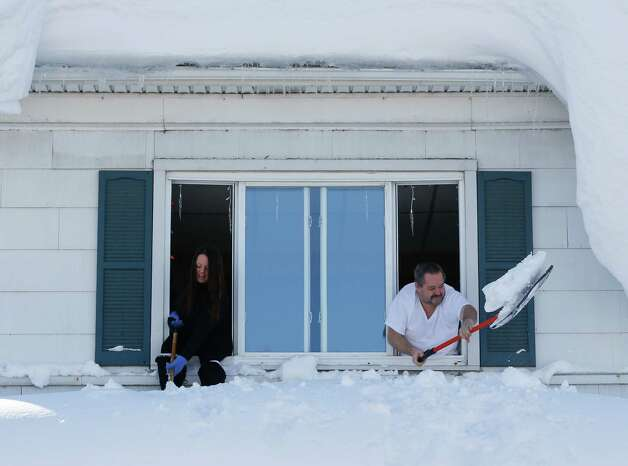 Residents clear snow from a porch roof while leaning from a second-story window in the south Buffalo area on Friday, Nov. 21, 2014, in Buffalo, N.Y. A snowfall that brought huge drifts and closed roads in the Buffalo area finally ended Friday, yet residents still couldn't breathe easy, as the looming threat of rain and higher temperatures through the weekend and beyond raised the possibility of floods and more roofs collapsing under the heavy loads. (AP Photo/Mike Groll) ORG XMIT: NYMG109 Photo: Mike Groll / AP