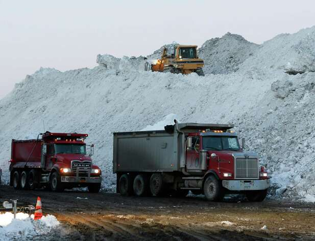 Dump trucks wait to unload snow at the Central Terminal that was removed from south Buffalo neighborhoods after heavy lake-effect snowstorms on Friday, Nov. 21, 2014, in Buffalo, N.Y. A snowfall that brought huge drifts and closed roads in the Buffalo area finally ended Friday, yet residents still couldn't breathe easy, as the looming threat of rain and higher temperatures through the weekend and beyond raised the possibility of floods and more roofs collapsing under the heavy loads.  (AP Photo/Mike Groll) ORG XMIT: NYMG103 Photo: Mike Groll / AP