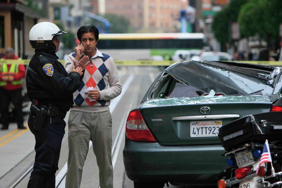 Mohammad  Alcozai, driver of the Toyota Camry that was crushed by the falling man, talks to an officer. Photo: Jessica Christian / The Chronicle / ONLINE_YES
