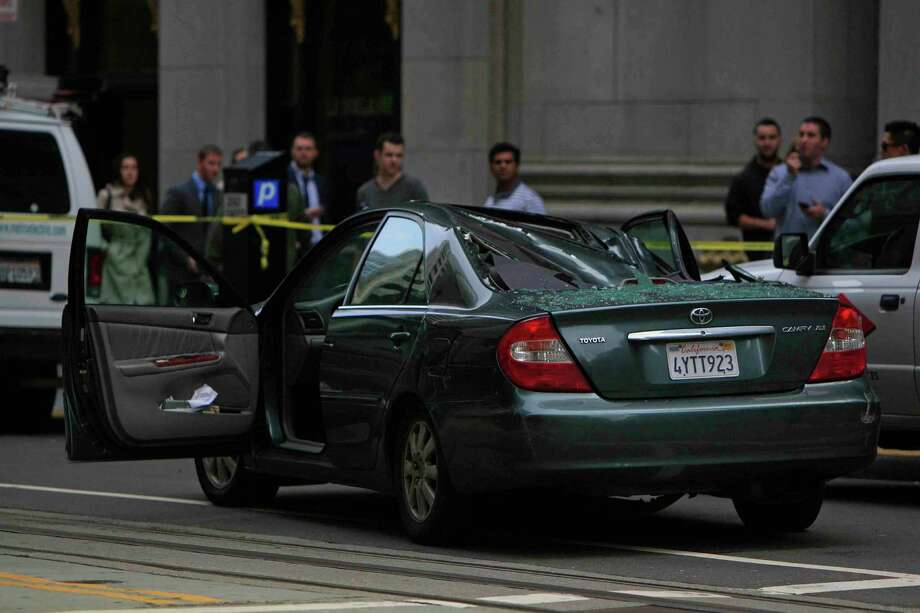 A 2002 Toyota Camry sits partly crushed after a window washer fell 11 stories onto its roof at Montgomery and California streets in San Francisco on Friday. Photo: Jessica Christian / The Chronicle / ONLINE_YES