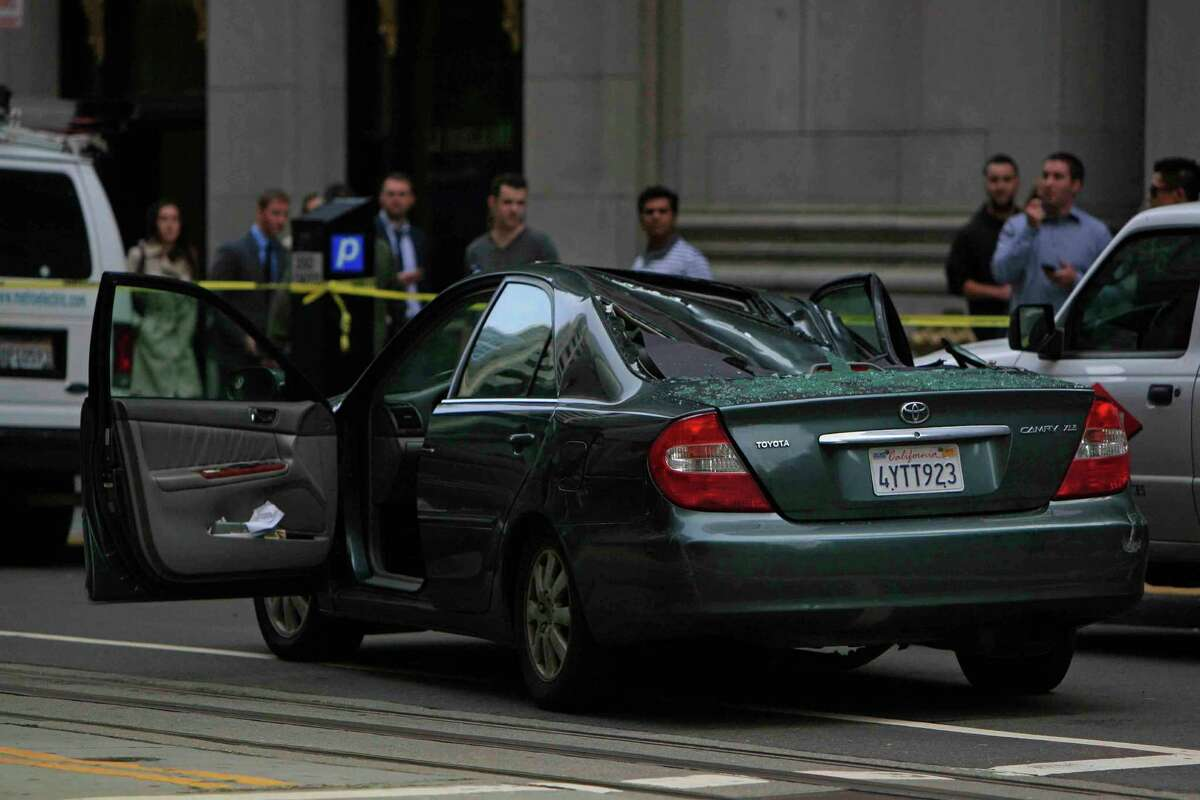 A 2002 Toyota Camry is crushed after a window washer fell 11 stories onto its roof at Montgomery and California streets in San Francisco on Friday.