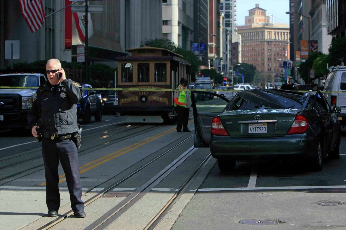 A police officer stands at the scene where a window washer fell 11 stories onto a moving car at Montgomery and California streets in San Francisco on Friday.