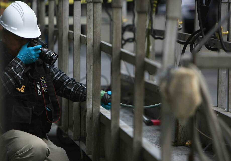An investigator takes photos of window scaffolding platform after a window washer fell 11 stories onto a moving car at Montgomery and California streets in San Francisco, Calif. Friday, November 21, 2014. Photo: Jessica Christian, The Chronicle
