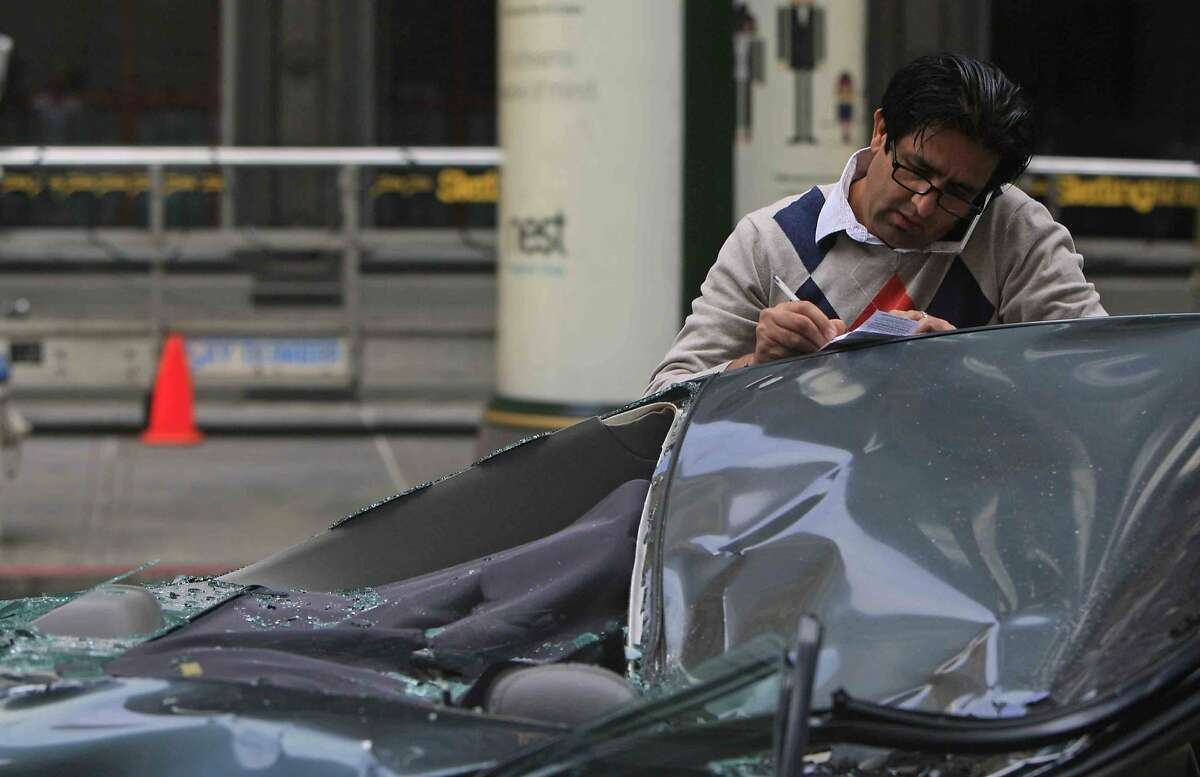 The driver of a 2002 Toyota Camry that was crushed after a window washer fell 11 stories onto its roof talks on the phone at Montgomery and California streets in San Francisco, Calif. Friday, November 21, 2014.