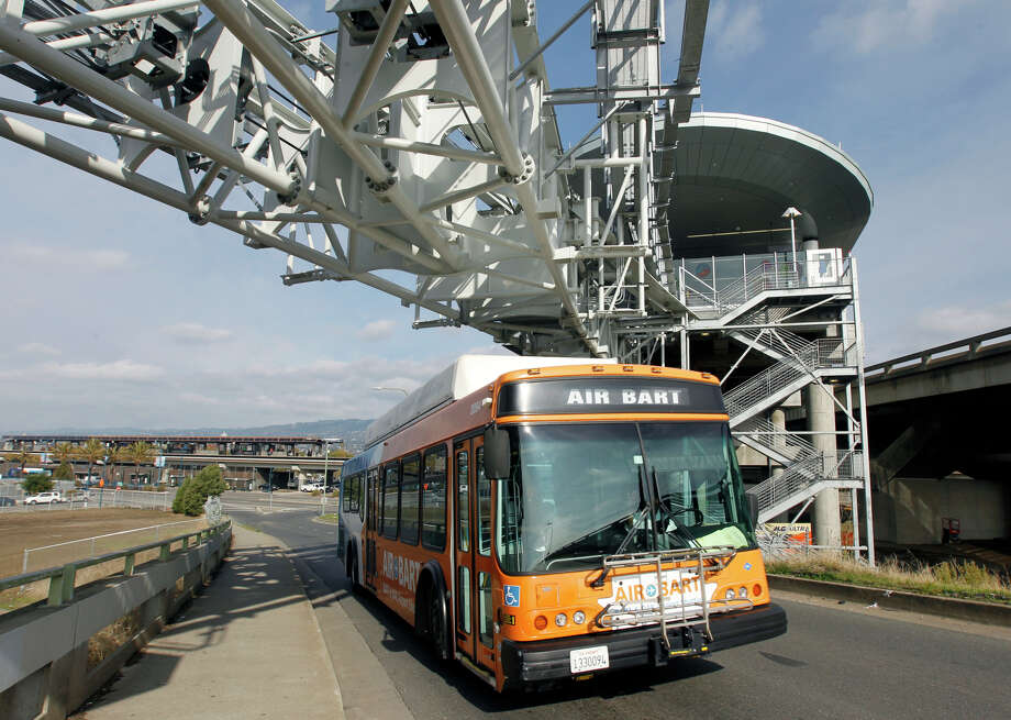An Air BART shuttle bus passes below tracks for the Oakland Airport Connector system on Friday. The buses will no longer run when the rail link providing a connection from the Coliseum Station to Oakland International Airport begins regular service Saturday. Photo: Paul Chinn / The Chronicle / ONLINE_YES