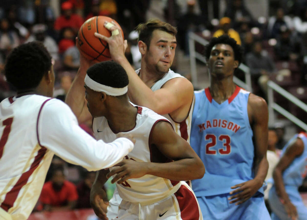 Cy Woods senior power forward Samir Sehic, center, controls a rebound in front of Madison senior center Chris Harris (23) during their game at the Campbell Center last week.