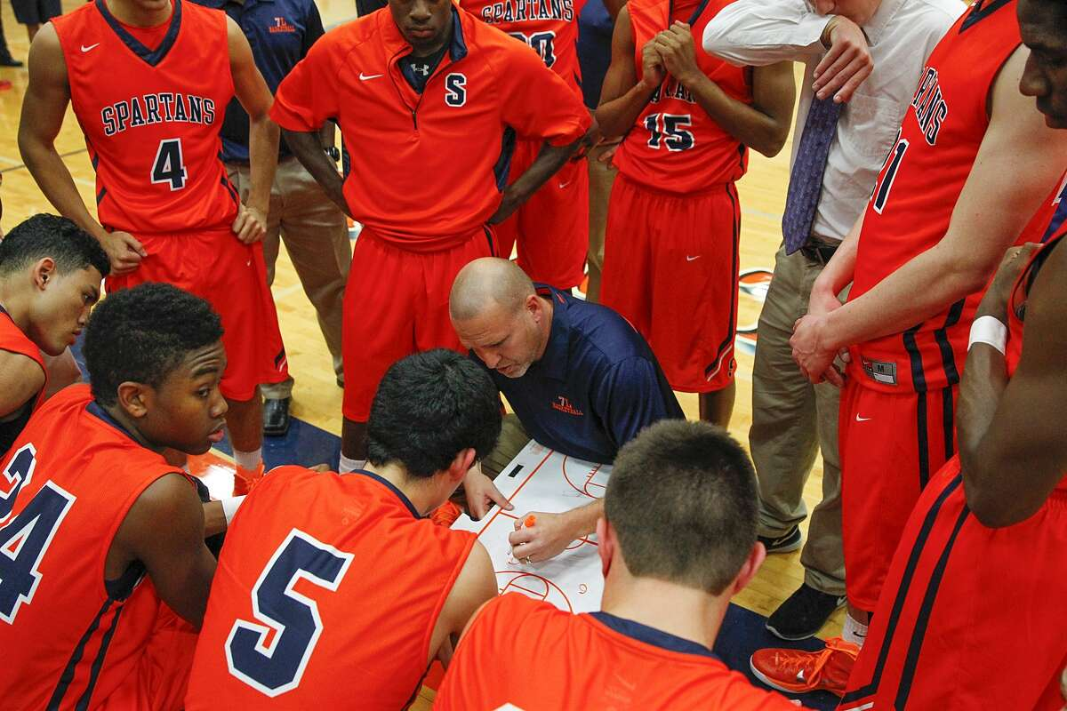 Seven Lakes head basketball coach Shannon Heston gives instructions to the players during a time out as the Spartans took on Cy Springs at Seven Lakes High School in Katy on November 18, 2014.