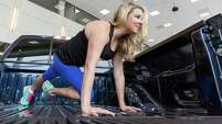 Cari Shoemate climbs into the bed of a pickup inside the showroom of Tommie Vaughn Ford to do a plank twist.