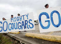 Jennifer Thompson, Sharon Santos, Amy Busby, and Wendy Morgan, left to right, hold up large signs of encouragement for the Buna High School football team Friday afternoon. Buna residents took to the sides of Highway 62 on Friday afternoon to see off the Buna Cougars as they head for their game against Rockdale at Klein Memorial Stadium. This is the farthest the school has gone in the playoffs since 1983. Photo taken Friday 11/21/14 Jake Daniels/The Enterprise