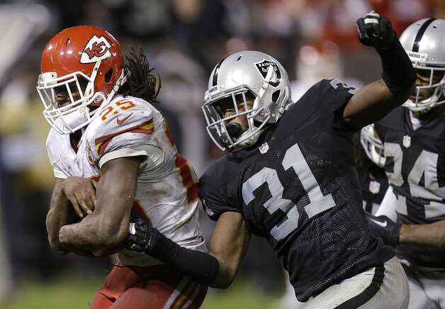 Kansas City Chiefs running back Jamaal Charles (25) runs past Oakland Raiders defensive back Neiko Thorpe (31) to score on a 30-yard touchdown reception during the fourth quarter of an NFL football game in Oakland, Calif., Thursday, Nov. 20, 2014. (AP Photo/Ben Margot)
