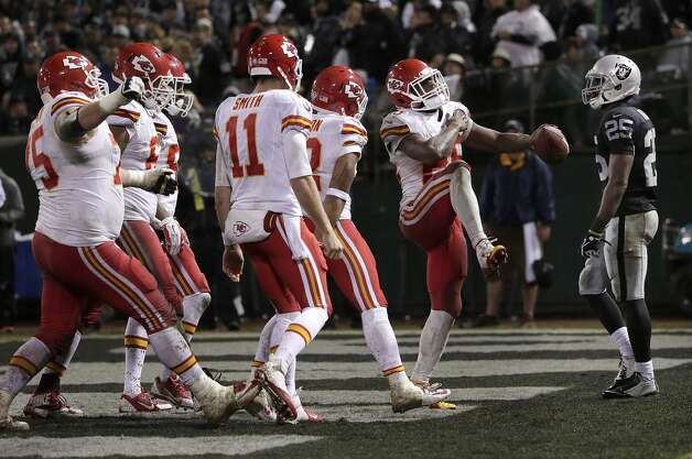Kansas City Chiefs running back Jamaal Charles, second from right, celebrates with teammates in front of Oakland Raiders cornerback D.J. Hayden (25) after scoring on a 30-yard touchdown reception from quarterback Alex Smith (11) during the fourth quarter of an NFL football game in Oakland, Calif., Thursday, Nov. 20, 2014. (AP Photo/Marcio Jose Sanchez)