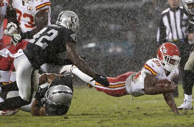 Kansas City Chiefs running back Jamaal Charles (25) falls forward after being tackled by Oakland Raiders outside linebacker Khalil Mack, bottom, as defensive back Larry Asante (42) approaches during the second quarter of an NFL football game in Oakland, Calif., Thursday, Nov. 20, 2014. (AP Photo/Marcio Jose Sanchez)