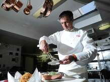 Four Star Chef Thomas Henkelmann prepares his upscale take on the Thanksgiving Day classic dish, green bean casserole, at Homestead Inn, Greenwich, Conn., Friday, Nov. 21, 2014.