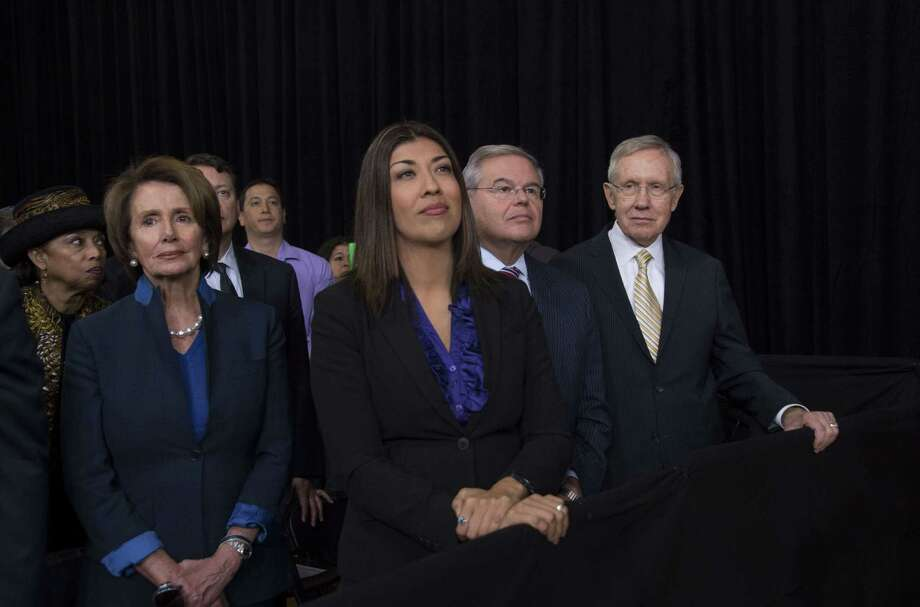 US Senator Harry Reid (R), D-Nevada, US Senator Bob Melendez (2nd R), D-New Jersey, and House Minority Leader Nancy Pelosi (L), D-California, look on as US President Barack Obama delivers remarks on the new steps he will be taking within his executive authority on immigration at Del Sol High School in Las Vegas, Nevada, November 21, 2014.       AFP PHOTO / Jim WATSONJIM WATSON/AFP/Getty Images Photo: JIM WATSON, Staff / AFP ImageForum