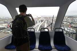 Jordan Olling photographs an Oakland Airport Connector train pull away from the airport station in Oakland, Calif. on Friday, Nov. 21, 2014. BART'S new rail link providing a seamless connection from the Coliseum station to Oakland International Airport begins regular service Saturday.